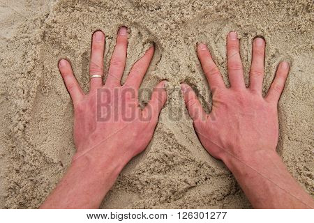 Male Caucasian Hand In The Salt Sand On The Beach.