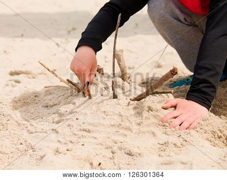Child's hands build stronghold in white salt sand and use broken twigs