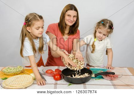 Two Little Girls At The Kitchen Table With A Zeal To Help Her Mother Pour The Mushrooms From The Pla