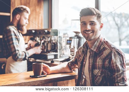 Enjoying best coffee in town. Young handsome man looking at camera with smile while sitting at bar counter at cafe with barista at the background