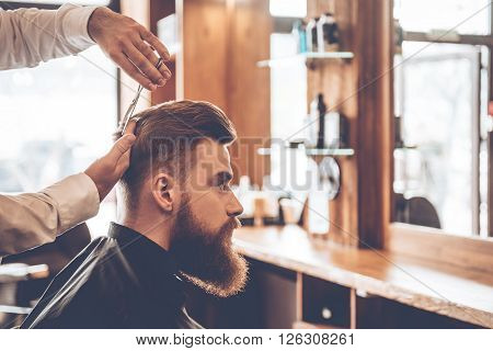 Perfect cut from back to front. Close-up side view of young bearded man getting haircut by hairdresser at barbershop