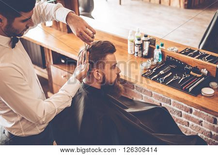 Haircut must be perfect. Top view of young bearded man getting haircut by hairdresser while sitting in chair at barbershop