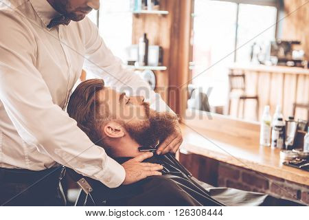 Making his beard look perfect. Close-up side view of young bearded man getting shaved with straight edge razor by hairdresser at barbershop