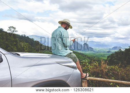 Young man traveler is watching video which he took on mobile phone during break between road trip in Asia.