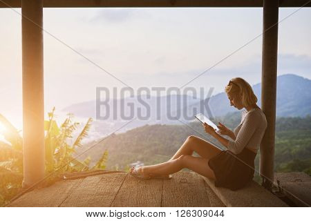 Female traveler is watching video on digital tablet while is sitting against amazing subtropical forest and sky background with copy space. Woman tourist is searching information on portable touch pad
