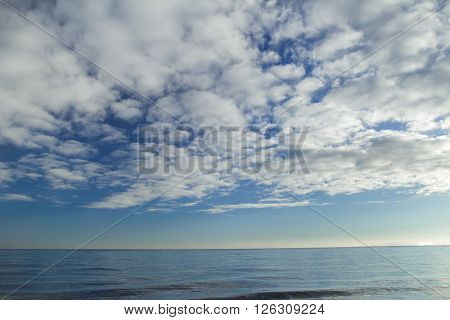 Cloudscape with stratocumulus clouds over sea horizon