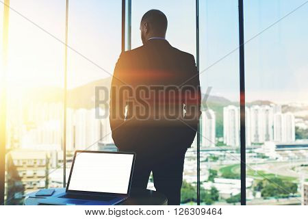 Silhouette of man CEO is thinking about future of his company while is watching in office window on a skyscrapers business center. Open net-book with mock up copy space screen is lying on the table
