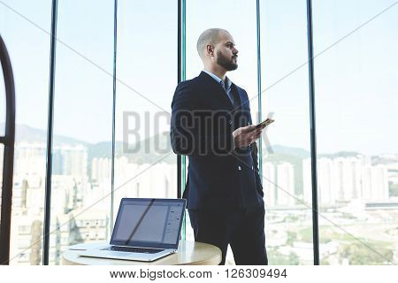 Confident man broker in suit is holding mobile phone while is standing in office of brokerage company near table with open portable net-book with blank copy space screen for your promotional content