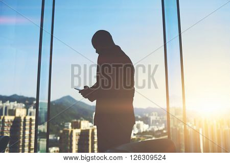 Silhouette of a man entrepreneur is typing text message on mobile phone to investor to consider again the question of funding while is standing in office near big skyscraper window with city view
