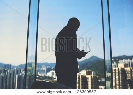 Silhouette of a man smart financier is calculating inefficient spending of enterprise by using mobile phone while is standing in his office near big window with view of business district in China