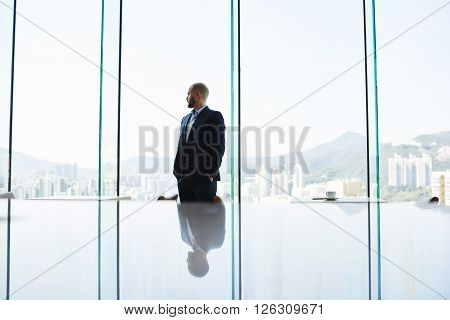 Thoughtful man proud CEO is thinking about new methods of management of the construction company. Entrepreneur is watching in office window Honk Kong city with tall skyscrapers. Copy space background