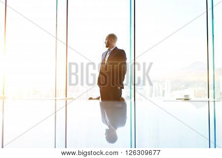 Young serious man managing director is waiting meeting with staff to hear the explanation why is not executed monthly plan company.Businessman is standing near office window with copy space background