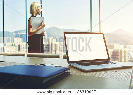 Young successful businesswoman with paper document in hands is looking in office window with view of Hong Kong city. Open laptop with mock up copy space screen for your content is lying on a table