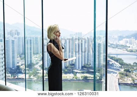 Serious confident woman lawyer is holding digital tablet and calling via cell telephone to her client to further refine your certain questions while is standing near office window with copy space