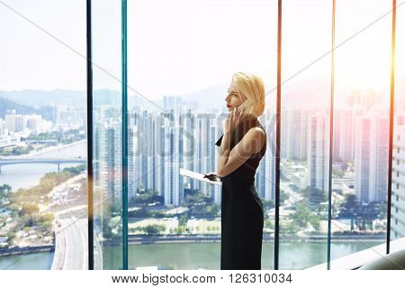Woman owner of successful enterprise with touch pad in hand having serious conversation with manager about the loss of new clients while is standing in skyscraper office interior during business trip