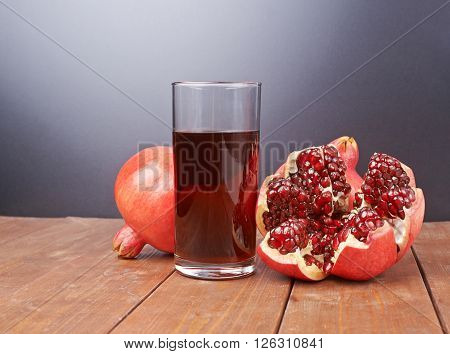 Pomegranate Punica granatum fruit next to the tall glass full of red juice, composition placed over the wooden boards surface poster