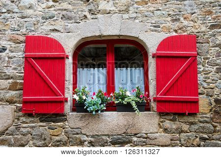 Window in old stone house with flowers  France Bretagne