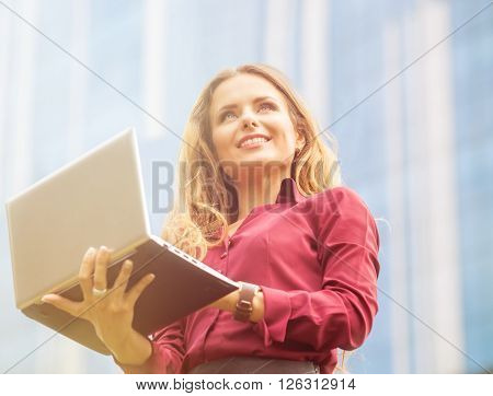 Smiling businesswoman holding laptop in her hands in front of office building. Beautiful lady in vivaceous blouse looking away in the city.