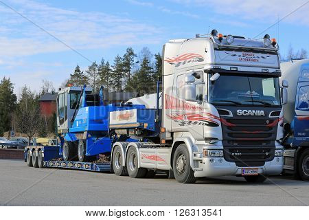 SALO, FINLAND - APRIL 15, 2016: Scania R580 is parked on a truck stop and is ready to deliver Terex Fuchs MHL 320 material handler on lowboy trailer.