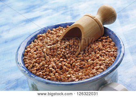 Buckwheat seeds into ceramic cup with wooden scoop. Slightly oblique photo.