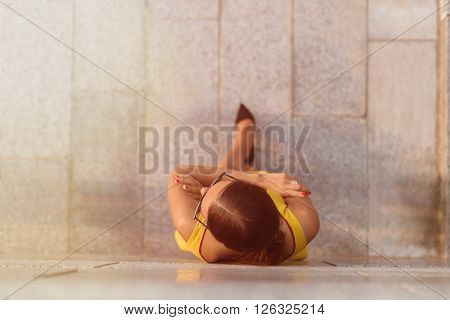 Top view of fashion girl standing near brick wall with her arms crossed. Girl in yellow dress and sunglasses posing for photographer. Toned image.