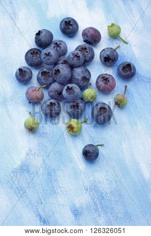 Blueberries from organic semi-wild cultivation over painted textile background. Some fruits unripe. Overhead view.