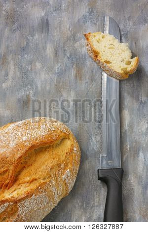 Bread and kitchen knife on painted textile background. Overhead view.
