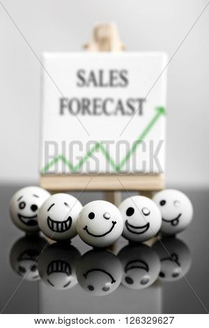 funny marbles with faces and a whiteboard in the background. concept sales forecast