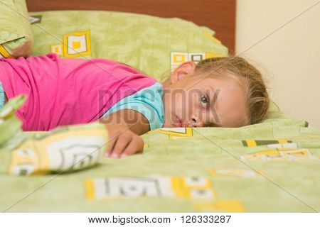 Six-year Girl Lying Across The Bed, Trying To Sleep