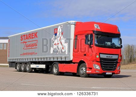 PAIMIO, FINLAND - APRIL 15, 2016: Red new DAF XF Euro 6 semi truck and curtainsider trailer of Starek Transport parked at a truck stop in South of Finland.