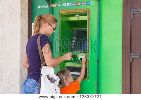 Anapa Russia - September 20 2015: A young girl with the child to withdraw money from the ATM Sberbank