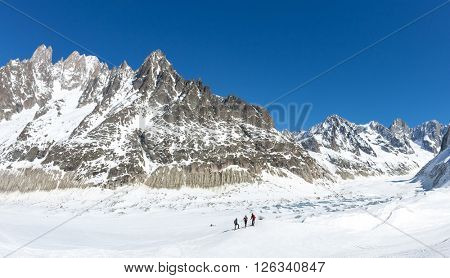 A group of skiers look at Leschaux Glacier, in the Mont Blanc massif, the highest mountain in Europe. Chamonix, France.