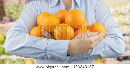 woman holding in her arms citric fruits like oranges at the greengrocer on the store background