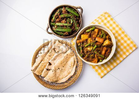 bhindi masala or bhendi masala or ladies finger fry with mixed veg in red curry with indian roti / chapati / fulka / paratha / indian bread, indian spicy food