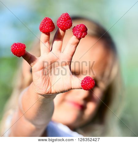Child's hand with raspberry on fingers, outdoors