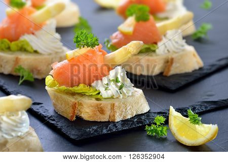 Delicious canapes with German white asparagus, cream cheese with herbs, smoked salmon on Italian ciabatta bread with lettuce leaves, served on slate boards
