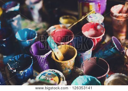 Multicolored plastic cans with paints. Artist workplace background. Old dirty Paints background. Colorful artist palette. Soft toned. Creativity, visual art concept. Art and craft. Closeup