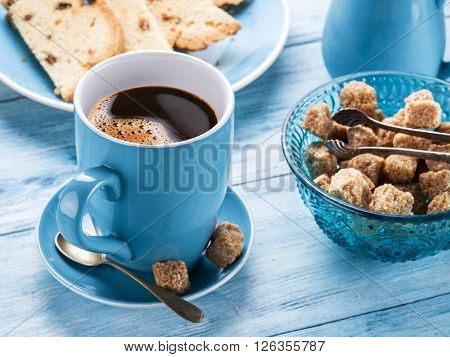 Cup of coffee, milk jug, cane sugar cubes and fruit-cake on old blu wooden table.