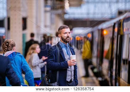 Hipster businessman holding a disposable coffee cup at the train station platform ** Note: Visible grain at 100%, best at smaller sizes