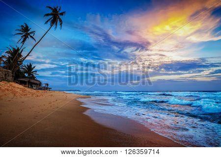 Beach holidays vacation romantic concept background - sunset on tropical beach with dramatic cloud sky. Sri Lanka