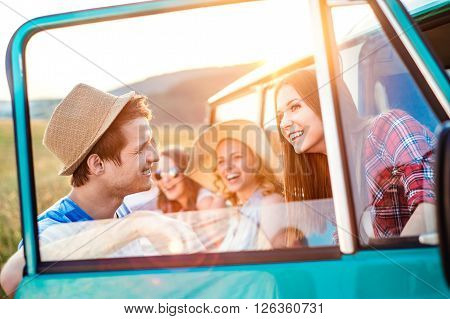 Group of teenage hipsters on a roadtrip having fun, standing at the campervan. Young friends outside on a summer day.