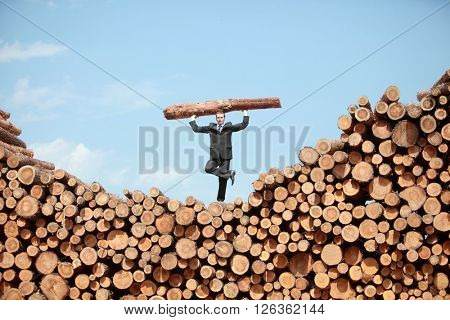 Balanced hardworking business man on top of large pile of logs   lifting  heavy log standing on one leg - front view