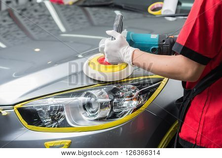 Car detailing series : Worker waxing grey car