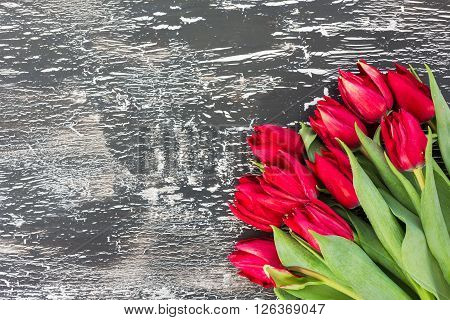 Bouquet Of Red Tulips On Black Wooden Background. Top View, Copy Space