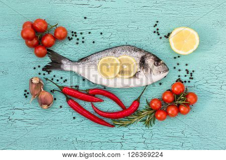 Raw Dorado Fish With Vegetables On Blue Table. Top View, Copy Space. Raw Bream Fish