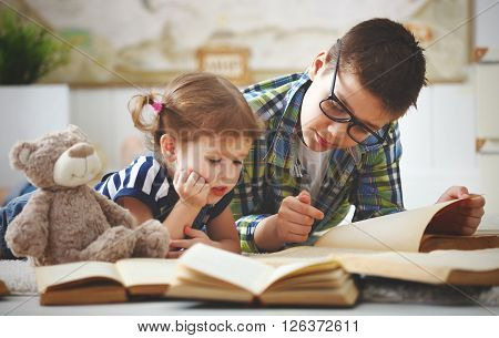 children brother and sister boy and girl reading a book at home