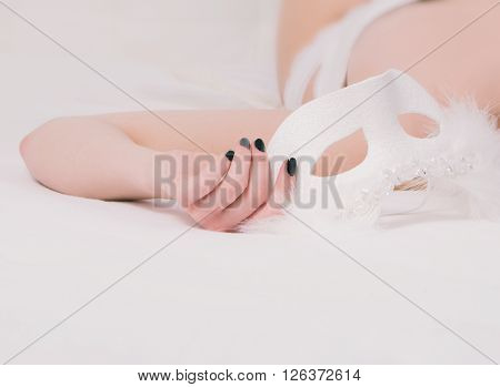 Hand of sexy young girl in white corset and panties underwear lying on the bed, holding white mask, body detail, no face, anonymous, beauty boudoir concept