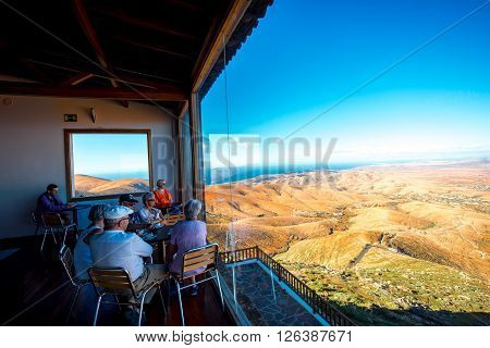 BETANCURIA, FUERTEVENTURA ISLAND, SPAIN - CIRCA JANUARY 2016: Tourists enjoy great view on the central part of Fuerteventura island near Betancuria village from the cafe at Morro Velosa viewpoint