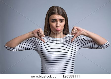 I do not like it. Cheerless beautiful young girl holding her fingers down and expressing disapproval while standing isolated on grey background