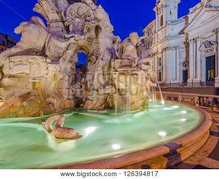 Illuminated at night the fontana del Moro (the Moor Fountain) on Piazza Navona on the Sant'Agnese in Agone church background, Rome, Italy